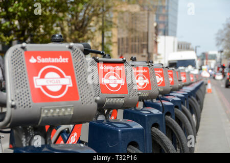 A row of parked bikes in a Santander Docking station on Blackfriars Bridge Road, London, UK - Stock Image