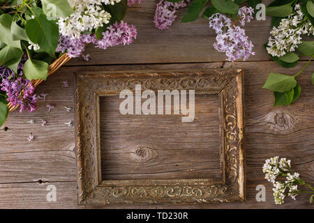 Decor of flowers on the background of vintage wooden planks.Vintage background with lilac flowers and place under the text. View from above. Flat lay. - Stock Image