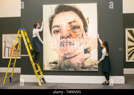 London, UK. 21st June, 2019. Sotheby's technicians with 'a Shadow Head', 2007-2013 by Jenny Saville, Oil on Canvas. Estimate: £3,000,000-5,000,000 at the Sotheby's Contemporary Art Auction preview for the Evening sale on 26 June Credit: amer ghazzal/Alamy Live News - Stock Image