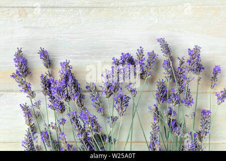 A fresh bouquet of blooming lavender flowers, shot from above on a rustic wooden background with copy space - Stock Image