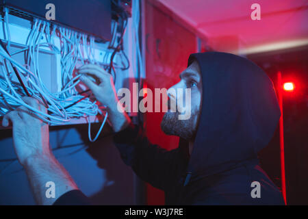 Serious concentrated young bearded network specialist in hoodie standing in dark room and examining cables of server - Stock Image