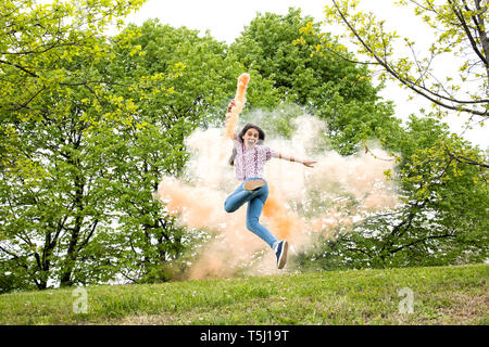 Agile excited young girl with a colored smoke flare running and jumping for joy in a wooded park or garden - Stock Image