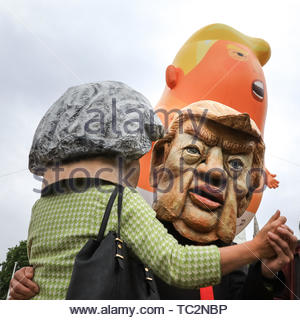 London, UK. 04th June, 2019. The Trump blimp hovers above dancing Theresa May and Donald Trump masked protesters in Parliament Square. People in central London protest against US President Donald Trump and his current visit to the United Kingdom. Credit: Imageplotter/Alamy Live News - Stock Image