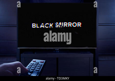 A man points a TV remote at the television which displays the Black Mirror main title screen (Editorial use only). - Stock Image