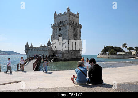 Rear back view of two young people sitting by the River Tagus Tejo riverside talking by Belem Tower historical building in Lisbon Europe KATHY DEWITT - Stock Image