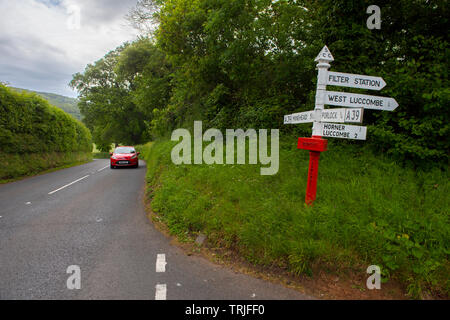 Exmoor Devon England UK. Road sign near Porlock. May 2019 Red Post or Finger Post sign post featured on modern Master Map Data. - Stock Image
