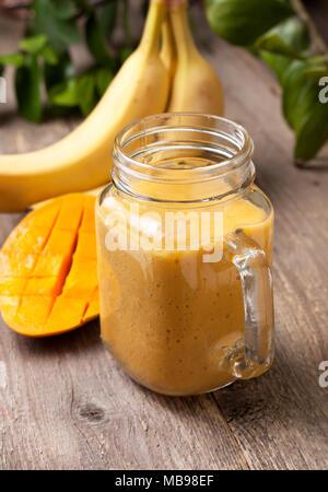 mango banana smoothie in Mason jar on old wooden background - Stock Image
