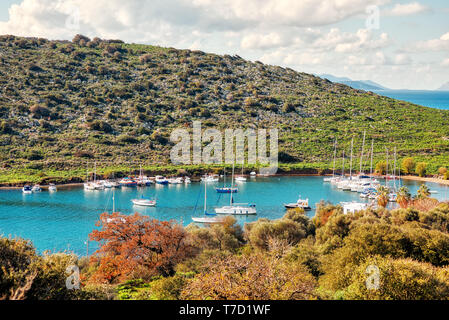 Yachts and boats anchored over the calm turquoise sea at gumsuluk bay in Bodrum, Mugla, Turkey. - Stock Image