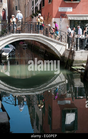 People crossing bridge Ponte Zaguri near Campiello de la Feltrinella with reflections under bridge in Venice  REFLECTIONS - Stock Image