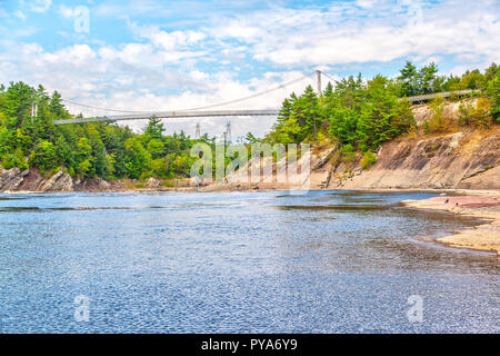 A 113 meter long suspension footbridge stands 23 metres over the Chaudiere River at Chutes-de-la-Chaudiere or Chaudiere Falls in Levis, Quebec. Archeo - Stock Image