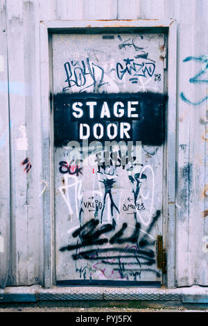 Stage door written on an old metal door covered in scribbles - Stock Image