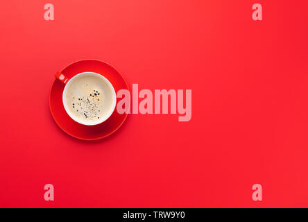 Red coffee cup over red background. Top view flat lay with copy space - Stock Image