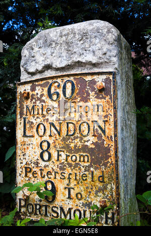 Old worn traditional milestone marker with metal plate stating 60 miles from London and 9 to Portsmouth - Stock Image