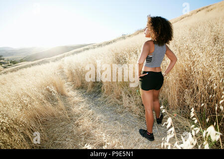 Young woman with curly brown hair standing on path in urban park. - Stock Image