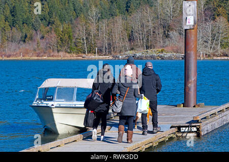 Four young people in winter garments carrying overnight bags to a moored boat.  Grant Narrows Regional Park, Pitt Meadows, B.C. Canada - Stock Image