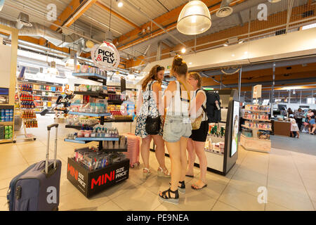 Three young women shopping in the duty free shop, Bordeaux-Merignac airport, Bordeaux, France Europe - Stock Image