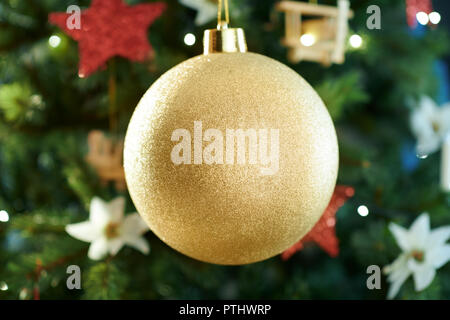 Closeup on big gold Christmas ball near Christmas tree - Stock Image