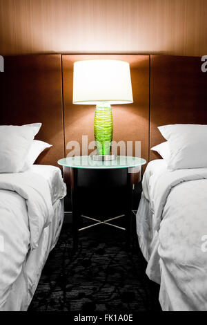Modern hotel room with a lamp in between two beds - Stock Image