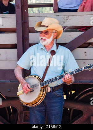 Banjo player entertains tourists on a train of the Kettle Valley Steam Railway, near Summerland BC Canada. - Stock Image