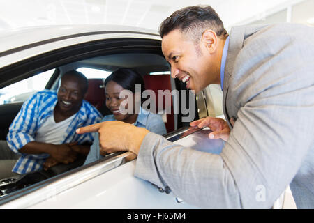 middle aged vehicle salesman showing new car to a happy young couple in showroom - Stock Image