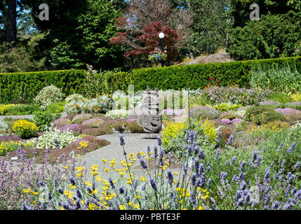 Gardens at Government House in Victoria, British Columbia, Canada with First Nations artwork. - Stock Image