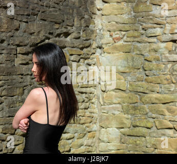 slim mexican woman standing in corner of a stonewall, naked shoulder - Stock Image