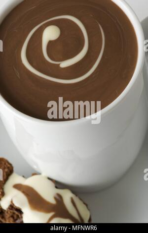 White porcelain cup with drinking chocolate. Almond and chocolate biscoti in saucer. Studio shot.      Ref: CRB538_103609_0013  COMPULSORY CREDIT: Mar - Stock Image