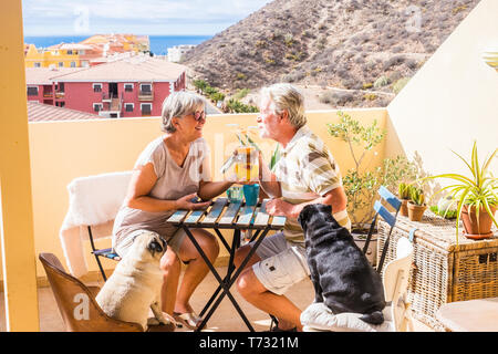 couple of aged senior gentlemen and lady drink together fruit juice on rooftop terrace wih two funny pug dog under the sunlight. amazing ocean view fo - Stock Image