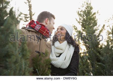 Couple shopping for Christmas tree - Stock Image