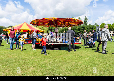 A children's merry-go-round carousel ride during the annual Bradford on Avon Lions fun-day with crowds watching and moving about - Stock Image