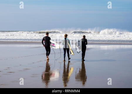 Three surfers with boards reflected in wet sand head in to the surf on the beach at Woolacombe, North Devon, England, UK, Britain - Stock Image