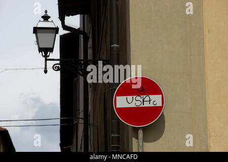 Spray painted grafitti on a street sign in spanish or italian indicating stop the USA or block the USA or dead end no entry to the USA - Stock Image