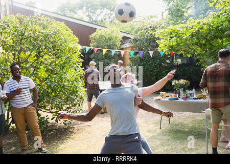Male friends playing soccer, enjoying backyard summer barbecue - Stock Image