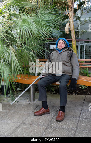 An elderly man with a walking aid asleep on a bench in a tropical setting. - Stock Image