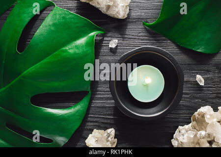 Lit Green Candle with Smoky Quartz and Monstera on Black Wood - Stock Image