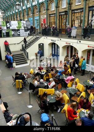 Crowds in Covent Garden watching and listening to a male tenor singing while eating and drinking - Stock Image