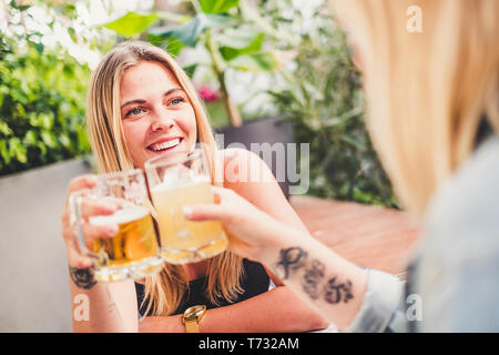 Cheerful blonde with friend at the bar drinking beer and celebrating in friendship toasting the glasses and having fun together - happy people celebra - Stock Image