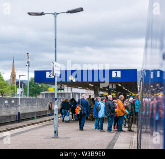 Fort William train station platform with people boarding ScotRail train on West Highland railway line, Scottish Highlands, Scotland, UK - Stock Image