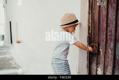 A small toddler boy with hat standing by a house in town on summer holiday, opening door. Copy space. - Stock Image