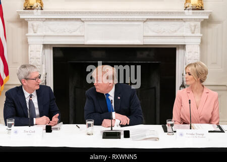 U.S President Donald Trump, center, listens to Apple CEO Tim Cook, left, as presidential daughter Ivanka Trump looks on during the American Workforce Policy Advisory Board Meeting in the State Dining Room of the White House March 6, 2019 in Washington, DC. - Stock Image