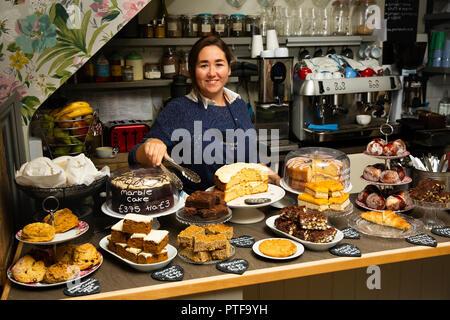 England, Berkshire, Goring on Thames, High Street, Pierrepont's Cafe, worker serving cakes - Stock Image