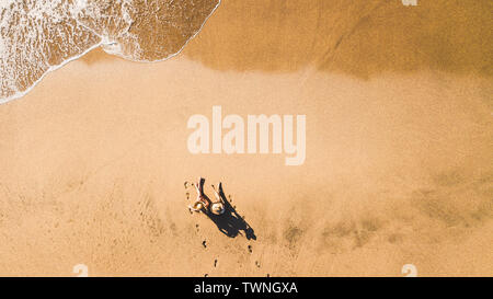 People enjoying vacation at the beach in resort hotel viewed  from vertical aerial pov - couple of girls sit down on the sand for summer holiday - tou - Stock Image