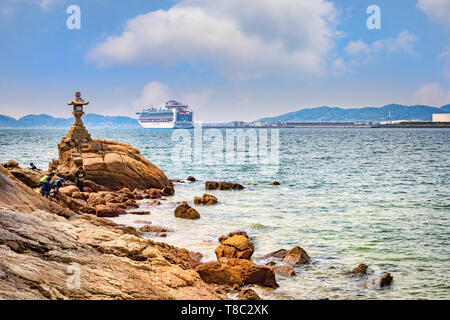 27 March 2019: Gamagori, Japan - The shore of the island of Takeshima, off Gamagori, with the cruise ship 'Diamond Princess' docked in the distance. - Stock Image