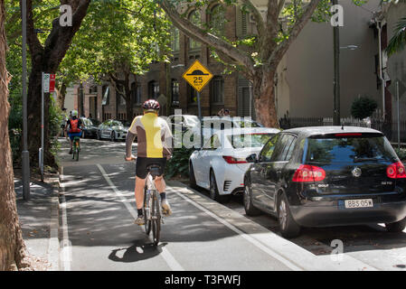 Cyclists using a dedicated bike or bicycle lane in the Sydney suburb of Surry Hillls, NSW, Australia - Stock Image