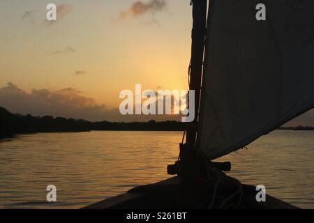 Dhow boat silhouette at sunset in Lamu, Kenya - Stock Image