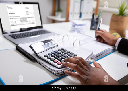 Close-up Of A Businesswoman Calculating Invoice Using Calculator Near Laptop - Stock Image