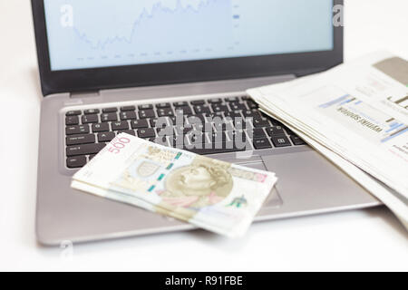 500 PLN banknotes, laptop and financial newspaper - Stock Image