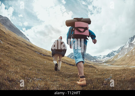 Two hikers in casual clothes and backpacks goes uphill in mountains - Stock Image