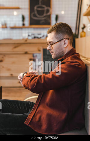 handsome man in burgundy shirt and black jeans sitting on couch and touching watch with fingein coffee house - Stock Image
