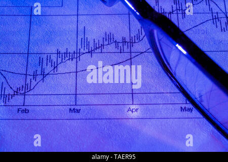 Close-up of black rimmed eyeglasses on top of blue paper financial performance graph, Studio Composition, Quebec, Canada - Stock Image